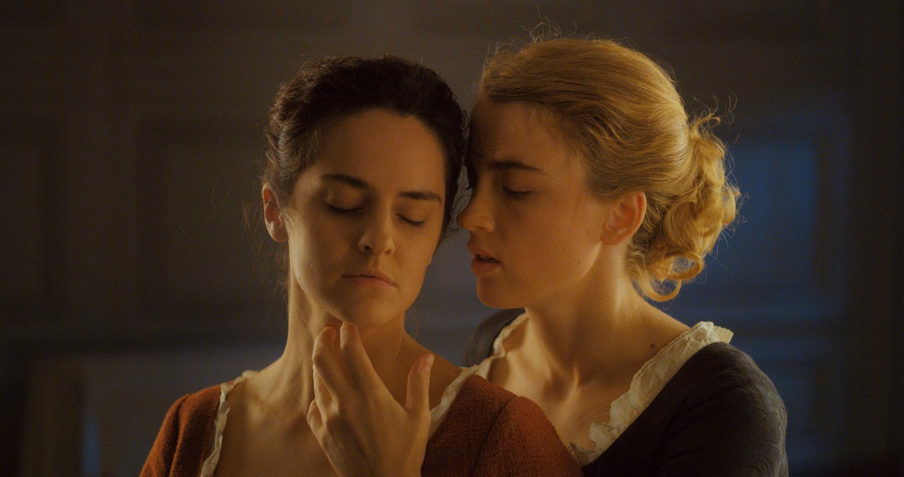 Cena em que Helóise, de olhos fechados e atrás de Marianne, também de olhos fechados, toca o queixo da pintora