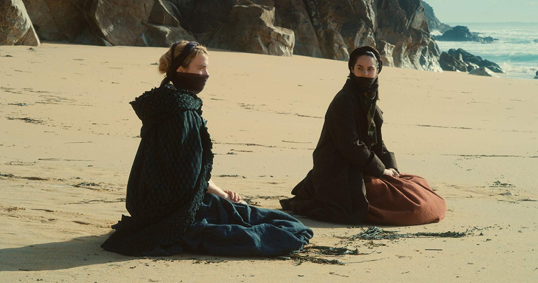 Héloïse (Adèle Haenel) e Marianne (Noémie Merlant) vestidas de forma que somente expõem os olhos e o cabelo, sentadas na areia, em uma praia.