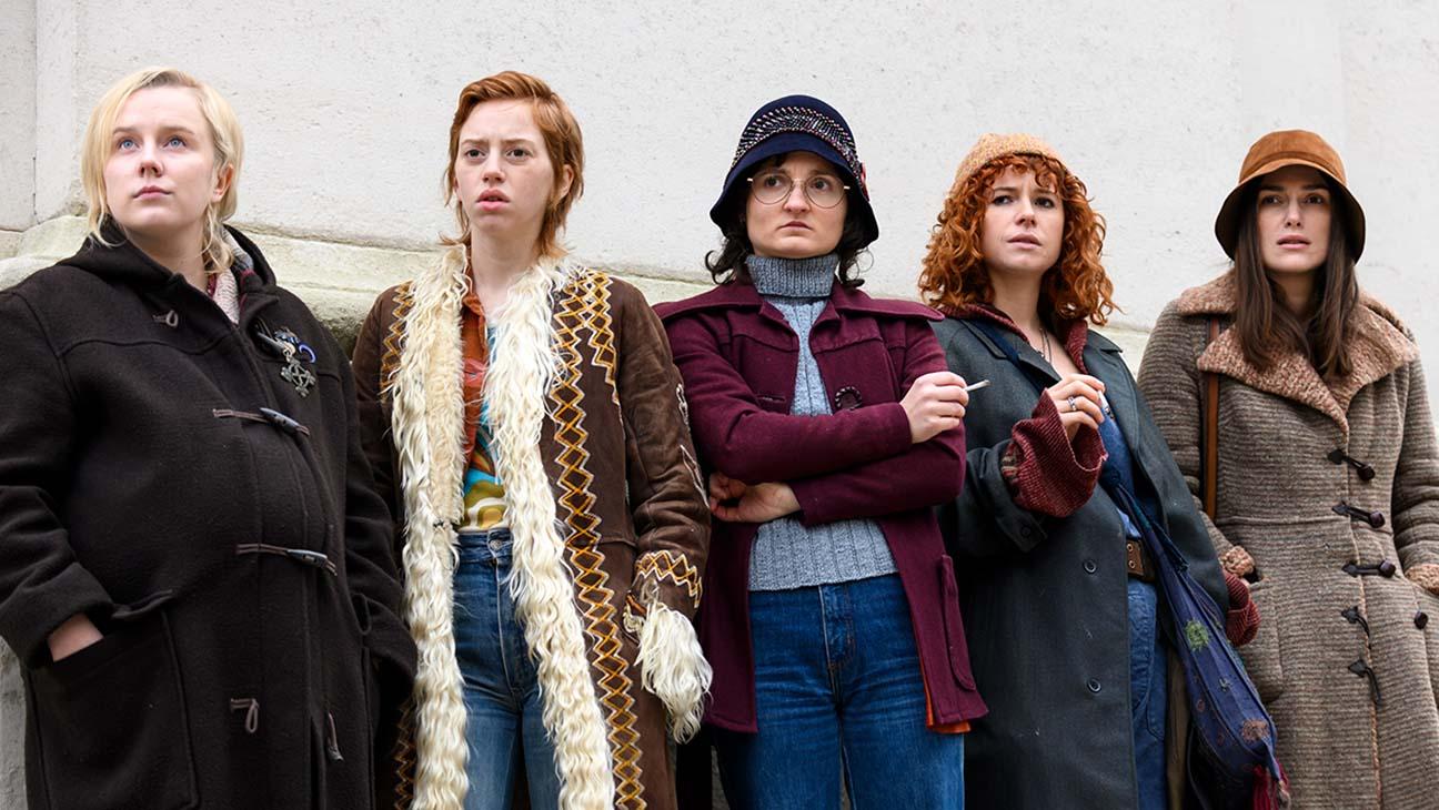 Na imagem, estão 5 personagens do filme, lado a lado, encostadas em uma parede.